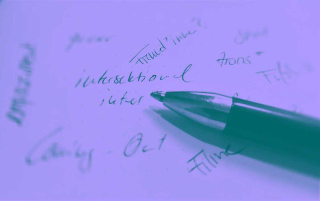 Ein Kugelschreiber liegt auf einem Blatt auf dem hanschriftlich verschiedene Worte stehen. Zu lesen sind zum Beispiel Freund*innen?, trans*, Filme, Coming-Out, inter, intersectional