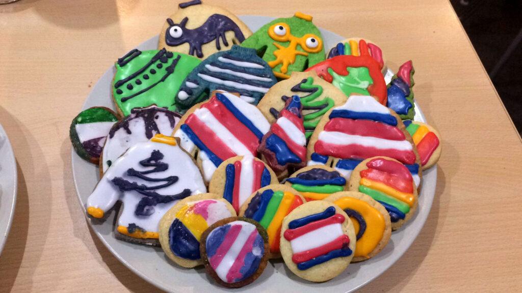 Selbstgebackene Kekse auf einem Teller. Viele Verzierungen zeigen queere Fahnen und Symbole.