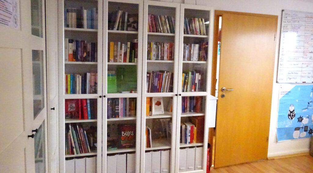 Die Mediathek vom Queeren Zentrum. Durch die Glasscheiben der Schranktüren sind Bücher, DVDs und Spiele zu sehen.