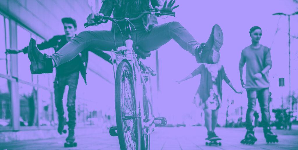 vier junge Menschen sind auf einer Straße unterwegs und bewegen sich auf die Kamera zu – zwei mit Rollschuhen, eine mit Skateboard und eine mit Fahrrad.
