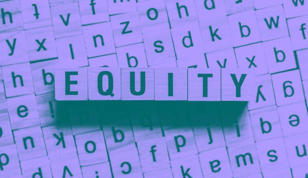 Das Wort EQUITY gelegt aus Holzwürfeln mit aufgedruckten Buchstaben.