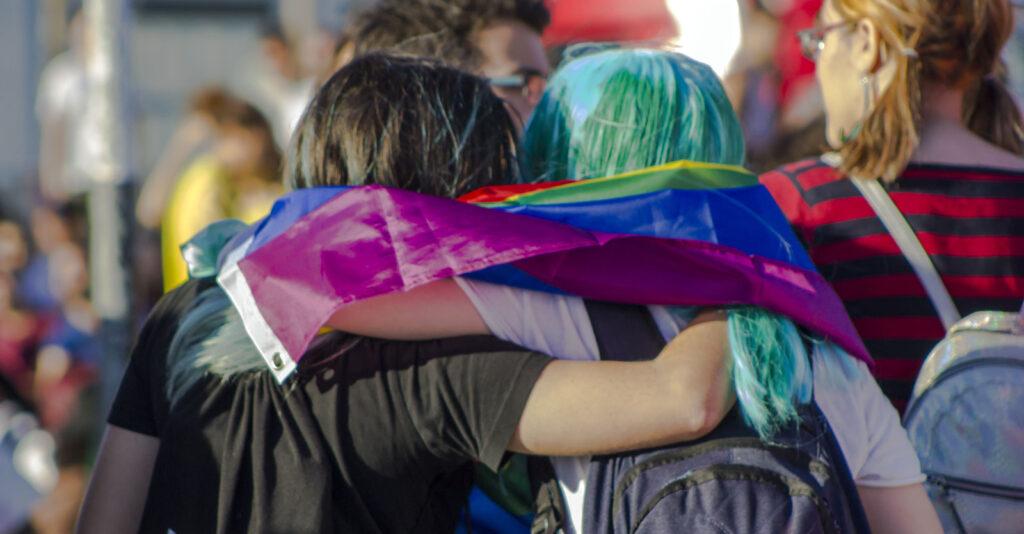 Zwei junge Personen haben sich gegenseitig einen Arm um die Schulter gelegt. Sie haben eine Regenbogenfahne umgehängt und gehen in einer Menschenmenge.