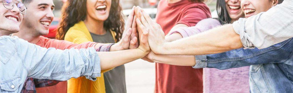 Mehrere lachende Personen stehen in einem Kreis, halten jeweils einen Arm nach innen und haben die Hände aufeinander gelegt.