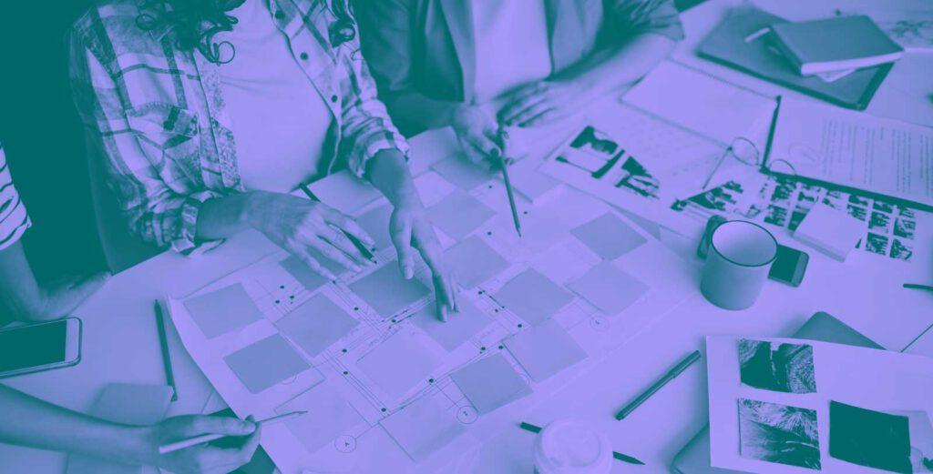 Blick von oben auf einem Tisch um den drei Personen sitzen. Auf dem Tisch liegen sehr viel Post-Its und andere Papiere.