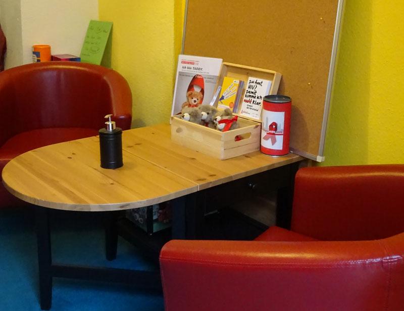 Eine der Beratungsecken im Zentrum. Zwei Sessel stehen vor einem kleinen Tisch auf dem eine Pinnwand steht.