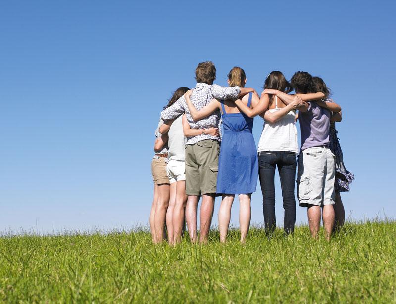 Eine Gruppe junger Menschen steht alleine auf einer großen Wiese im Kreis. Sie haben sich gegenseitig die Arme auf die Schultern gelegt.