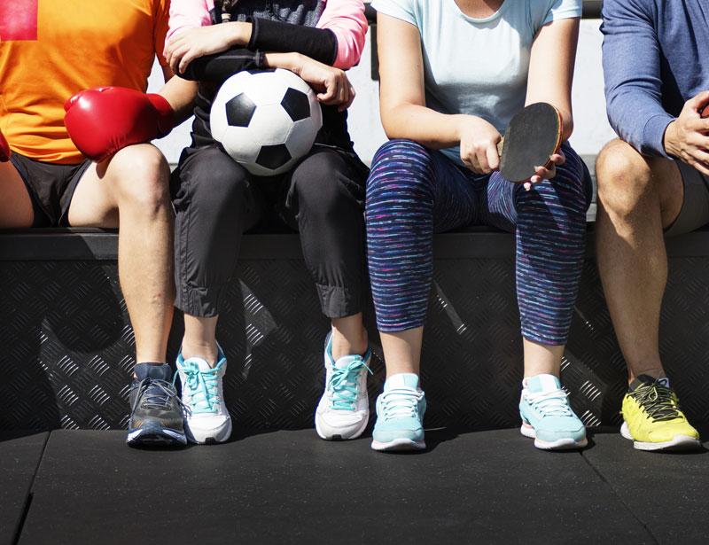 Verschiedene Personen, die von der Brust an abwärts zusehen sind, sitzen sportlich gekleidet auf einer Bank. Eine Person trägt Boxhandschuhe, eine einen Fußball und eine einen Tischtennisschläger
