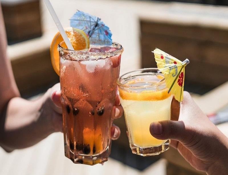 Zwei volle Cocktailgläser, die jeweils von einer Hand gehalten werden. Jeweils verziert mit Schirmchen und Orangenscheibe. Das linke Glas ist größer und enthält eine dunklere Flüssigkeit, das rechte ist zitronengelb.